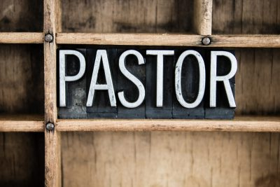 "The word ""PASTOR"" written in vintage metal letterpress type in a wooden drawer with dividers."